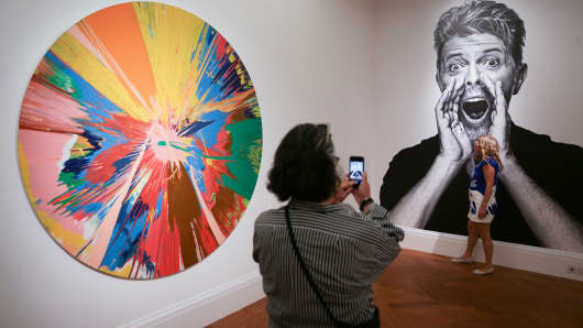 Visitors take a picture in front of a pictures of David Bowie and beside by one of the artworks (L) he owned named BEAUTIFUL, SHATTERING, SLASHING, VIOLENT, PINKY, HACKING, SPHINCTER PAINTING' by British artist Damien Hirst, at Sotheby's in London.