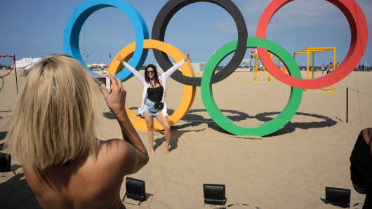 A woman poses for a photo by a set of Olympic rings on Copacabana beach in Rio de Janeiro on August 4, 2016 on the eve of the opening of the Rio 2016 Olympic Games.