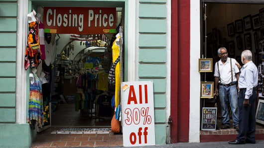 Two men speak outside a store displaying a 'Closing Price' sign in Old San Juan, Puerto Rico, on Friday, April 29, 2016.
