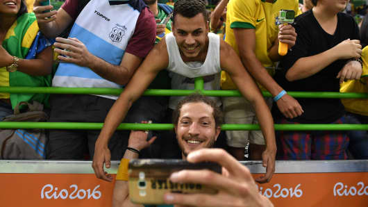 Brazil's right wing Fabio Chiuffa (front) poses for a selfie with fans as he celebrates their victory at the end of the men's preliminaries Group B handball match Poland vs Brazil for the Rio 2016 Olympics Games at the Future Arena in Rio on August 7, 2016.