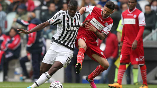 Juventus' midfielder Paul Pogba from France fights for the ball with Carpi's midfielder Marco Crimi during the Italian Serie A football match Juventus Vs Carpi on May 1, 2016.