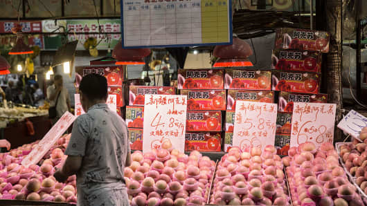 A man shops for apples at a fresh produce market in Shanghai in July.