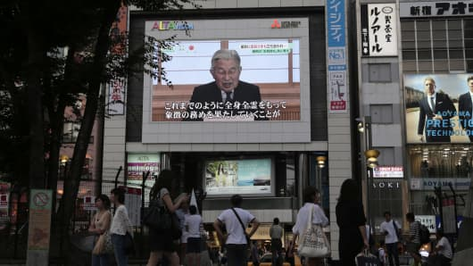 Pedestrians walk past a screen broadcasting a speech by Japan's Emperor Akihito in Tokyo on Monday, Aug. 8, 2016. Emperor Akihito, head of the world's oldest hereditary monarchy, said in a televised message he was concerned that it would become difficult for him to carry out his duties, weeks after reports that he had expressed a desire to abdicate