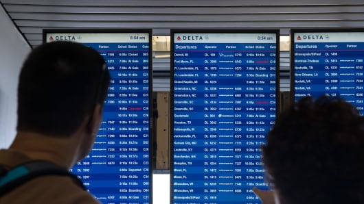 Travelers check the Delta departures board at LaGuardia Airport , August 8, 2016.