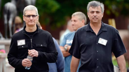 CEO Tim Cook (L) and senior vice president of Internet Software and Services Eddy Cue of Apple speak as they walk after lunch during the Allen & Co. annual conference at the Sun Valley Resort on July 11, 2013 in Sun Valley, Idaho.