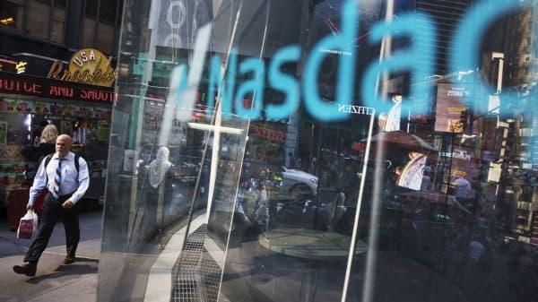 Pedestrians walk past the Nasdaq MarketSite in New York.