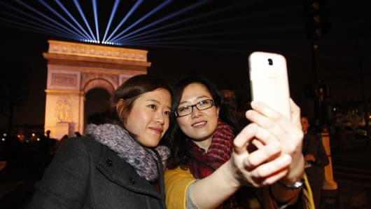 Tourists from China take a selfie in front of the Arc de Triomphe in Paris.