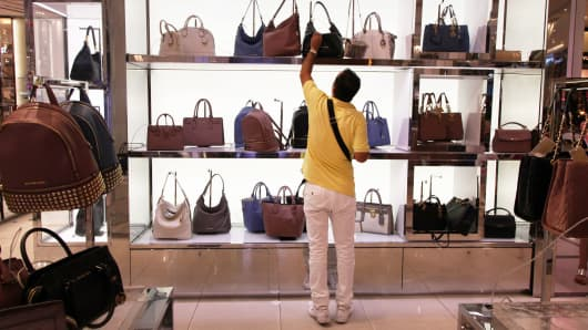 A shopper looking at Michael Kors handbags in Macy's flagship store in New York.