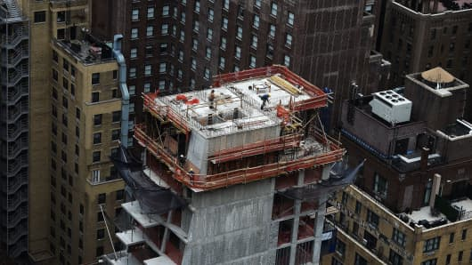 Construction laborers work on the top floor of a high rise apartment building in New York on March 31, 2105.