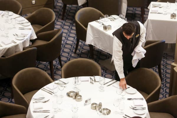 A waiter lays a table in the main dining hall on board Royal Caribbean Cruise's Harmony of the Seas Oasis.