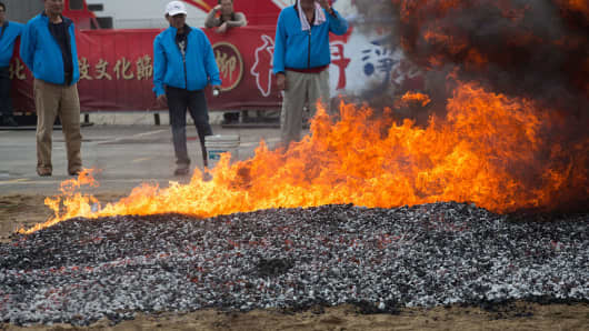 Preparing hot coals for a ritual where local temples will carry God icons across the fire. The annual harbour cleansing ritual is to ensure safety at sea and a bountiful catch in the year ahead, and takes place on the day of the first full moon in the Chinese lunar calendar.