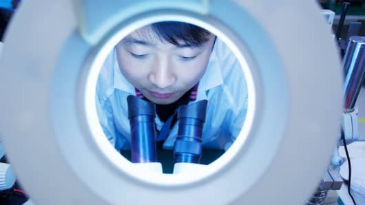 Worker at small parts manufacturing factory in China looking through microscope. The country's July industrial output grew by 6 percent on-year, slightly below market expectations.
