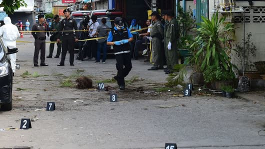 Investigation officials collect evidence from the crime scene after a small bomb exploded in Hua Hin on August 12, 2016.
