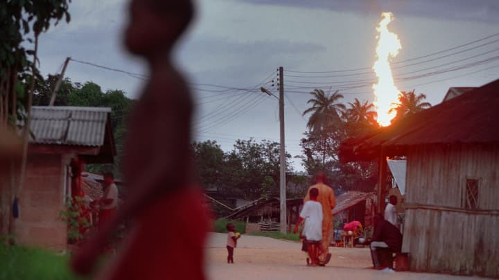 Villagers mill about the dirt streets of the impoverished village of Akaraolu, Nigeria while the two-hundred-foot tall Oshie gas flare looms constantly in the background.