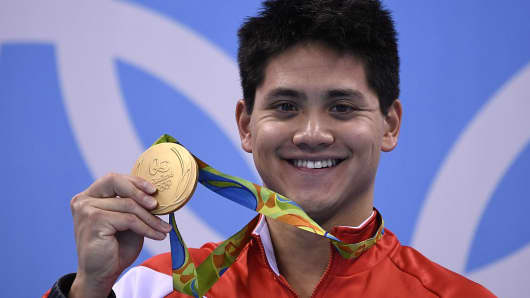 Singapore's Joseph Schooling poses with his gold medal on the podium of the Men's 100m Butterfly Final during the swimming event at the Rio 2016 Olympic Games at the Olympic Aquatics Stadium in Rio de Janeiro on August 12, 2016.