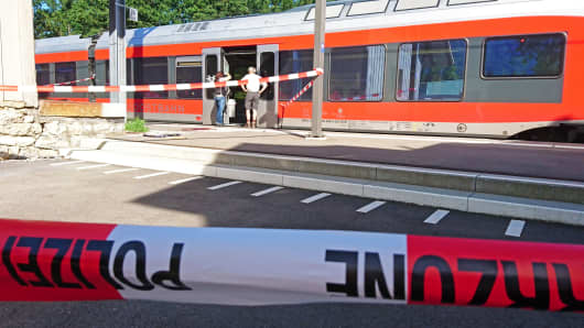 Policemen stand by a train at the station in Salez, eastern Switzerland, after a man set a fire and stabbed passengers on August 13, 2016.