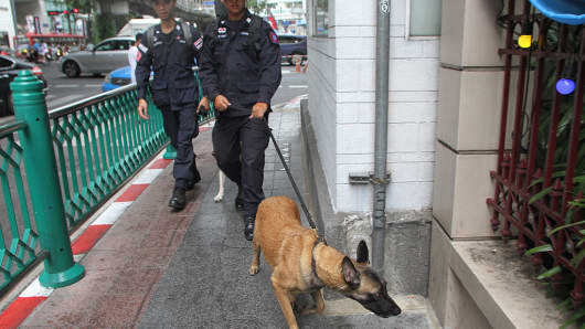 Thai police officer K9 unit patrols security at Erawan Shrine ( Phra Phrom ) in Bangkok to build confidence among tourists after several explosions in the southern Thailand.