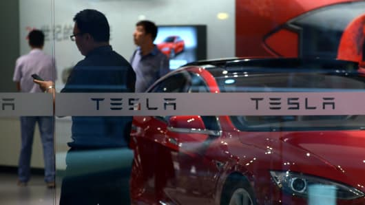 People visit a Tesla showroom in Beijing.