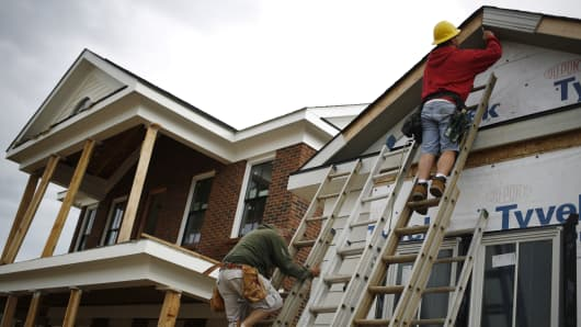 Contractors install siding on a house under construction in the Norton Commons subdivision of Louisville, Kentucky.