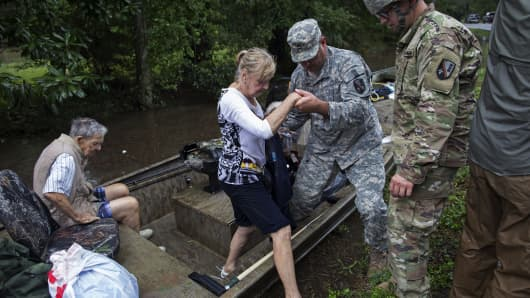 Members of the Louisiana Army National Guard rescue people from rising floodwater near Walker, La., after heavy rains inundated the region, Sunday, Aug. 14, 2016.