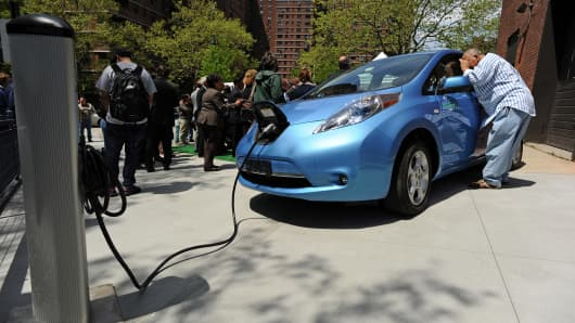 A man looks into a Nissan Leaf electric car that is plugged into a charging station at the Seward Park Co-op apartments on the Lower East Side of Manhattan.