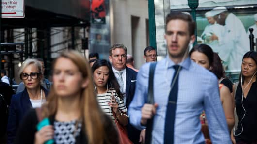 Pedestrians walk along Wall Street