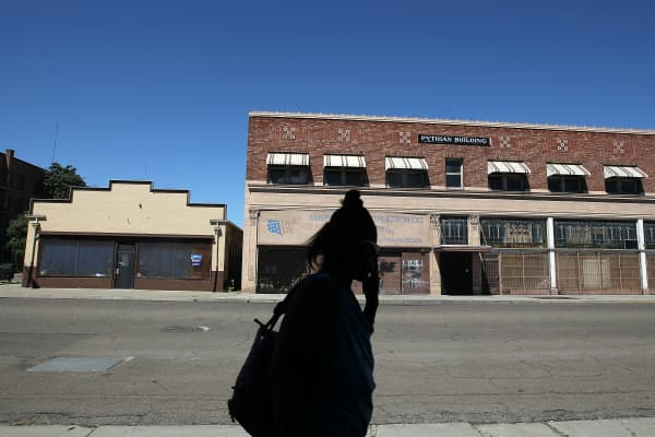A pedestrian walks by vacant buildings in Stockton, California.
