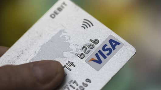 Visa Inc. and contactless payment logos sit on a debit card.