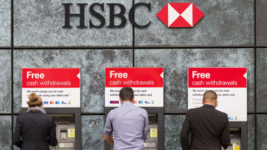 Customers use ATM cashpoints outside a HSBC bank branch in London on June 9, 2015.