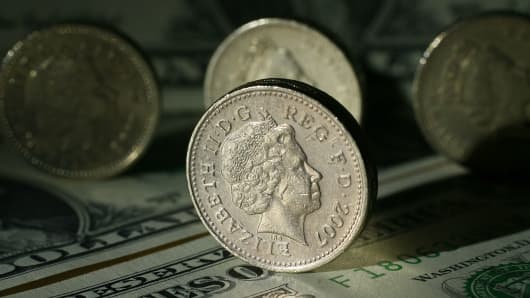 British pound coins can be seen next to American Dollar notes.