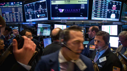 Traders work beneath a monitor displaying Valeant Pharmaceuticals International Inc. signage on the floor of the New York Stock Exchange.