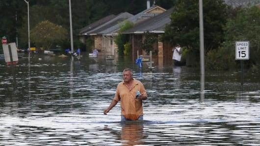 A man wades through a flooded street in Ascension Parish, Louisiana, U.S., August 15, 2016.