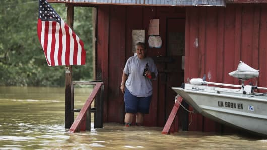 A person is seen on the front porch of a home as it is surrounded by flood waters on August 16, 2016 in Port Vincent, Louisiana.