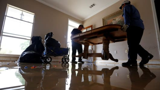 2016Clay Tassin and Pete Hildebrand remove a flood damaged dining table out of their coworker, Vanessa Bailey's (not pictured) house in Denham Springs, Louisiana.