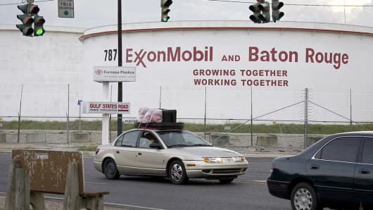 A car loaded with belongings drives past an Exxon Mobil Corp. refinery in Baton Rouge, Louisiana.
