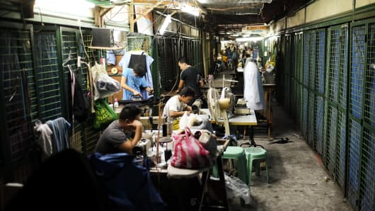 Tailors work on items of clothing at a tailoring shop at Kamuning market in Quezon City, Metro Manila, the Philippines, on Friday, May 20, 2016.