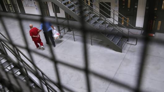 A guard escorts an immigrant detainee from his 'segregation cell' back into the general population at the Adelanto Detention Facility. The facility is managed by the private Geo Group.