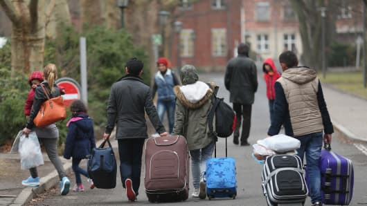People pulling suitcases arrive at the Central Registration Office for Asylum Seekers on March 11, 2015 in Berlin, Germany.