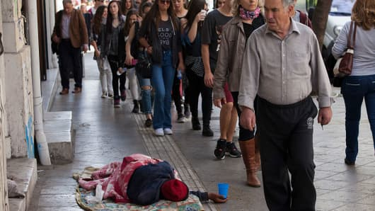 People walk past a homeless man asleep on a sidewalk still holding the cup he uses to beg for money, on April 8, 2016 in Athens, Greece.