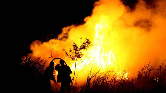 Indonesian men put out a fire in Ogan Ilir, southern Sumatra on October 22, 2015.