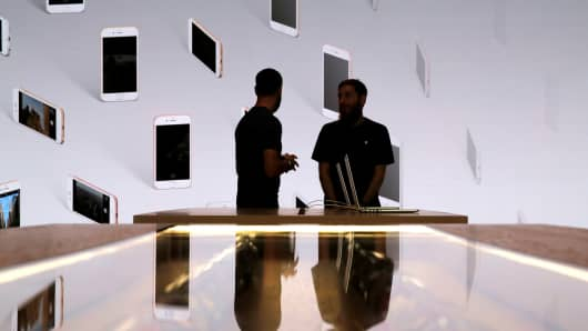 Store employees stand in front of a screen displaying iPhones at an Apple Store in Brooklyn, New York.