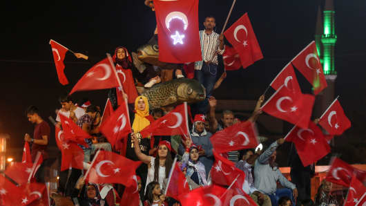 People hold Turkish flags and Turkish President Recep Tayyip Erdogan's posters as they gather to protest failed military coup attempt at Besyol Square in Van, Turkey on August 10, 2016.