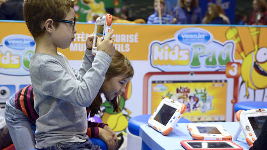 Children play with digital tablets at an expo in Paris, France on October 19, 2013. Engaging children and introducing them to technology early on has been the focus of many companies around the world.