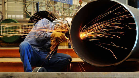 A Chinese worker polishes steel at an offshore oil engineering platform in Qingdao, China.