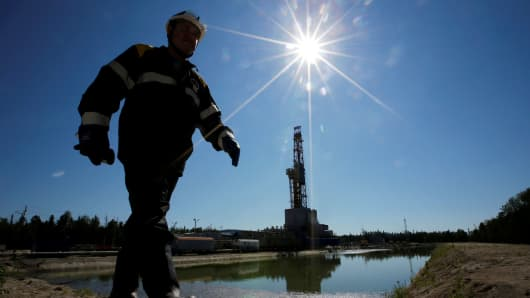 A worker walks past a drilling rig of the Rosneft-owned Prirazlomnoye oil field outside the West Siberian city of Nefteyugansk, Russia.
