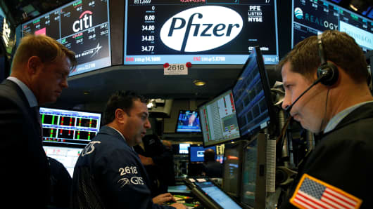 Traders gather at the post of Pfizer on the floor of the New York Stock Exchange in New York.