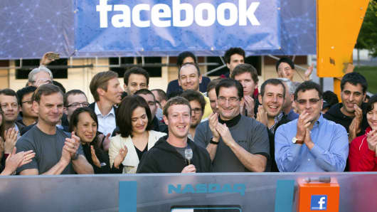 Facebook CEO Mark Zuckerberg (center) speaks remotely from Facebook's Menlo Park, California, campus for the opening of trading at Nasdaq MarketSite. COO Sheryl Sandberg (center left) and Robert Greifeld, (center right), CEO of Nasdaq OMX Group, also attended.