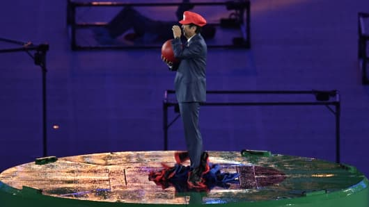 Japanese Prime Minister Shinzo Abe, dressed as Super Mario, holds a red ball during the closing ceremony of the Rio 2016 Olympic Games at the Maracana stadium in Rio de Janeiro on August 21, 2016.
