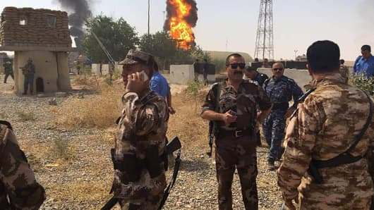 Peshmerga soldiers standing guard as smoke and flames billow from oil silos following an attack by militants on a gas facility in Iraq's northern Kirkuk province on July 31, 2016. Gunmen travelling on motorbikes opened fire on the gas facility's guards, then killed four of its employees and planted multiple bombs before escaping, officials from Iraq's North Oil Com