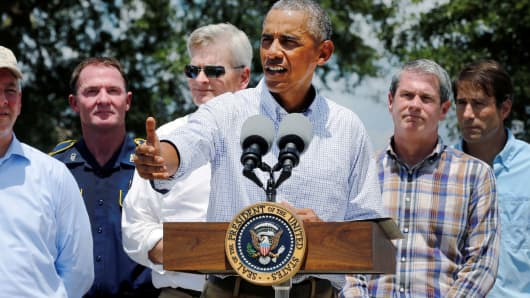 President Barack Obama, flanked by elected officials delivers remarks after touring a flood-affected neighborhood in Zachary, Louisiana, August 23, 2016.